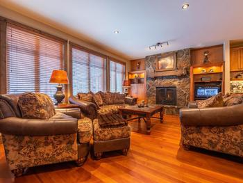 Large open living area with natural woods finishing. Cozy up to the fireplace, or relax with family and friends.