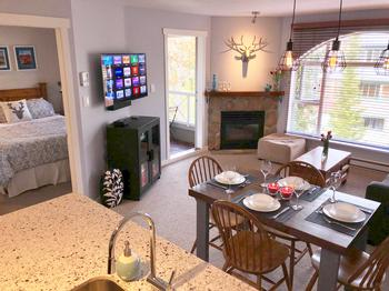 Open kitchen to spacious living area with fireplace and balcony.