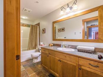 The shared bathroom has a combination of a bathtub and shower, heated floors and a vanity. The counter space and under counter storage has ample space for your toiletries.