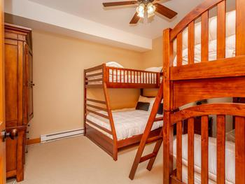 Bunk Room that sleeps 5 . Entertainment and wardrobe hutch with a TV and over 90 channels of programming.