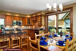 View of the dining room and gourmet kitchen, which includes all Jennair appliances. The table seats 8 comfortably. There is an extra leaf if you need even more space!