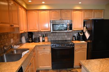 Well equipped kitchen includes large refrigerator, dishwasher, microwave oven, granite countertops and large island.