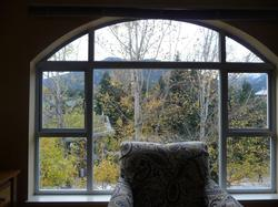 Lovely cathedral window frames the mountain and forest view.