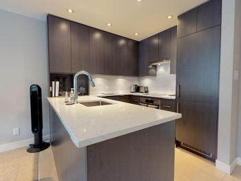 Modern fully equipped kitchen, overlooking dining and lounge area.